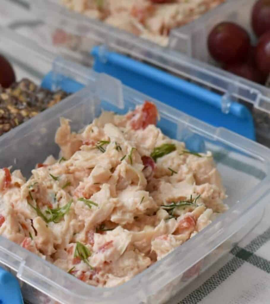 chicken salad in a meal prep container next to grapes