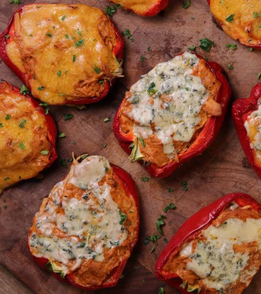 buffalo chicken stuffed peppers on a cutting board topped with parsley