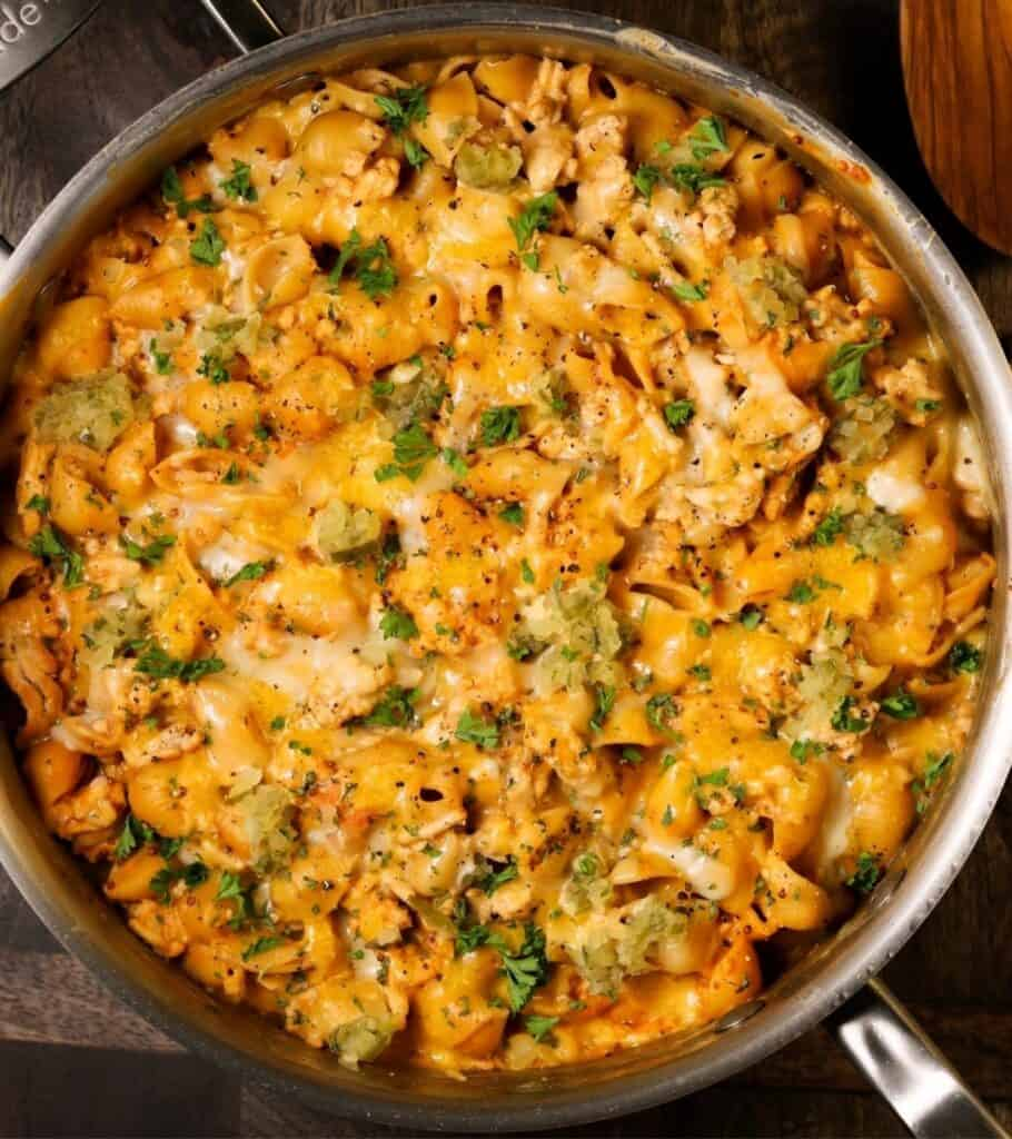skillet with cheesy pasta topped with parsley and dill relish
