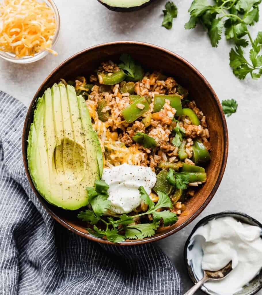 bowl with stuffed peppers filling, sour cream, cilantro, and a sliced avocado