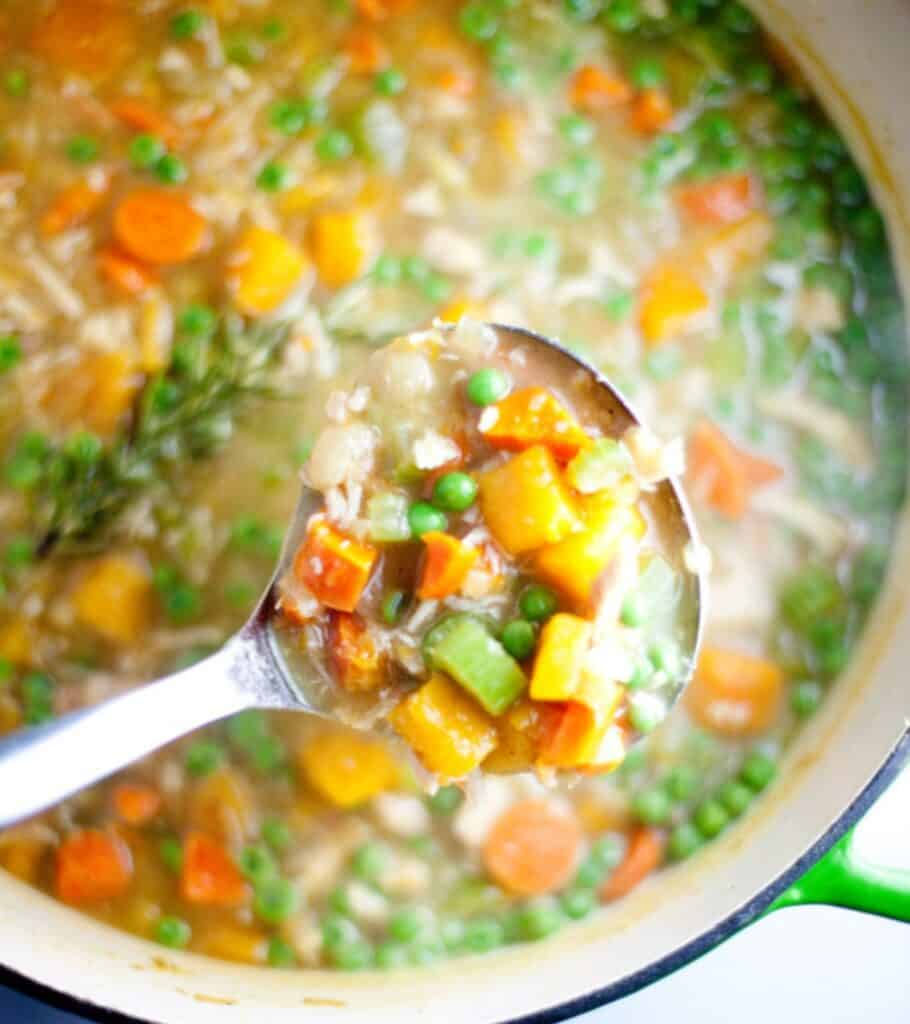 vegetable chicken soup in a pot with a ladle inside