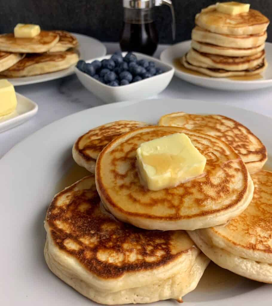 stack of protein pancakes with butter and syrup with blueberries and more pancakes in the background