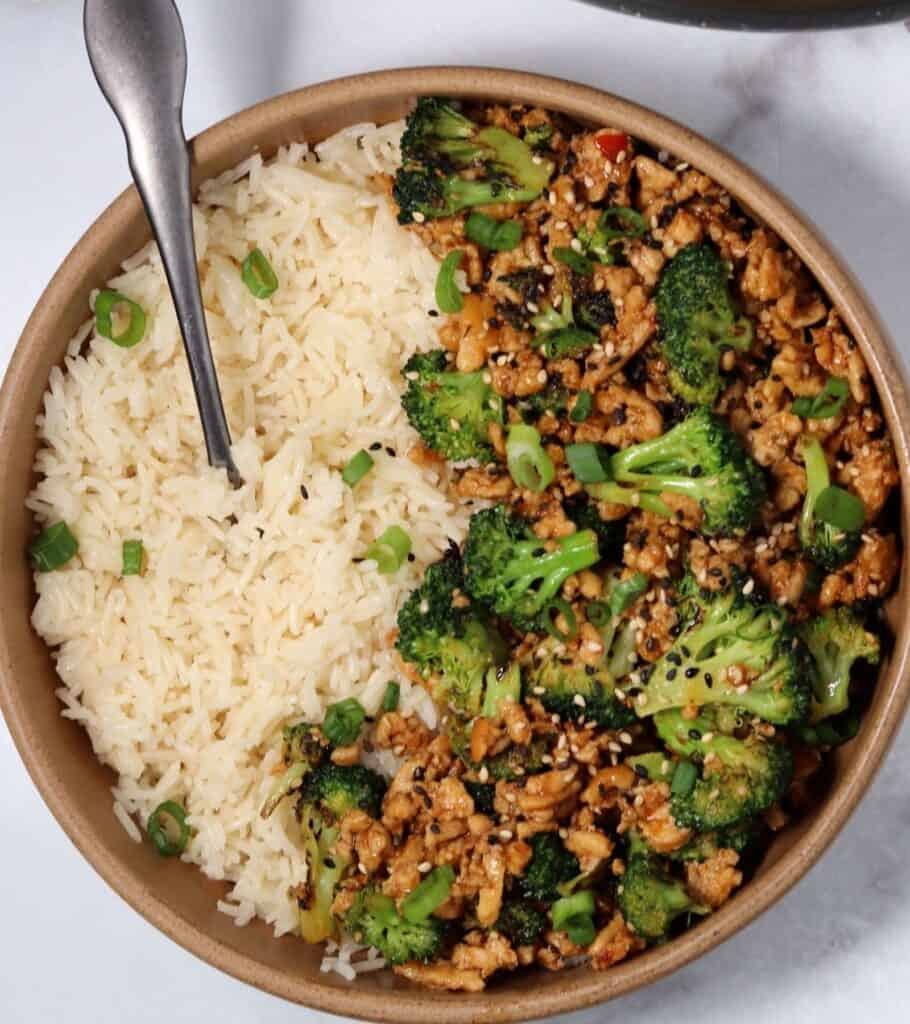 brown bowl with ground chicken, broccoli, green onion, sesame seeds, and rice