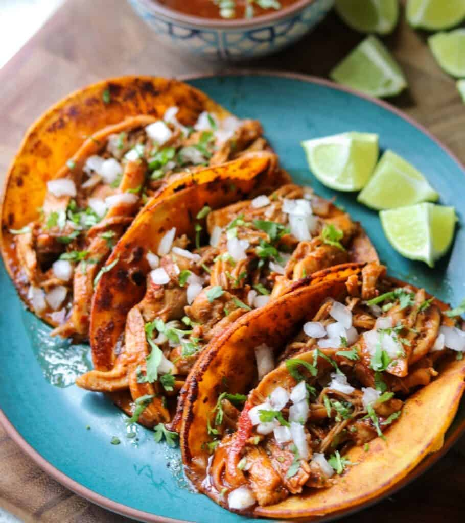 three birria tacos on a green plate with lime wedges
