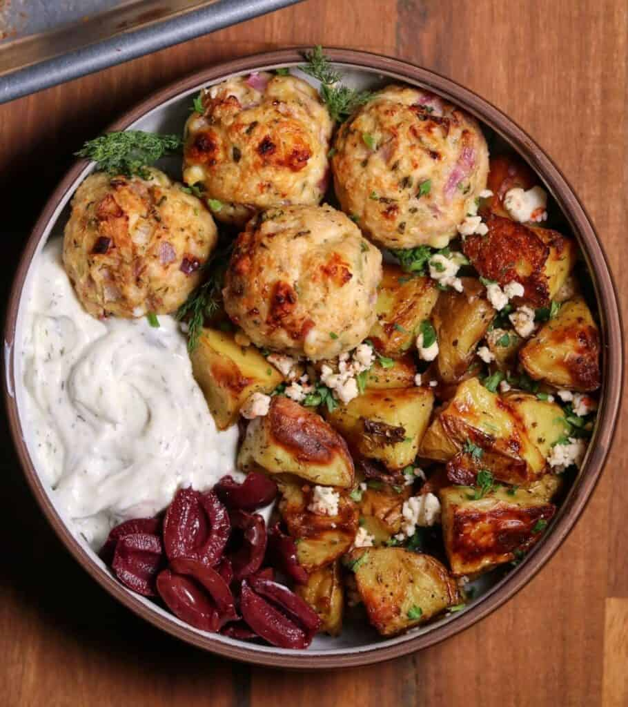 Greek meatballs and potatoes in a bowl with fresh dill, Kalamata olives, and Tzatziki sauce