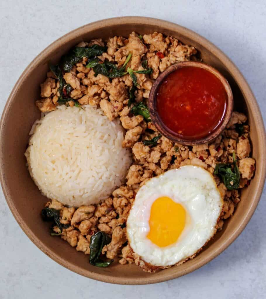 Thai basil ground chicken in a brown bowl with a cup of jasmine rice, fried egg, and small bowl of sweet chili sauce