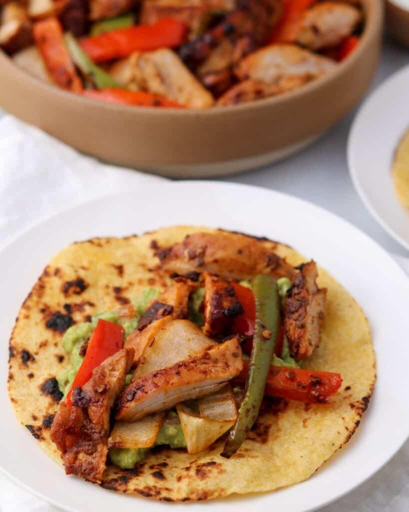 chicken fajitas on a tortilla with guacamole