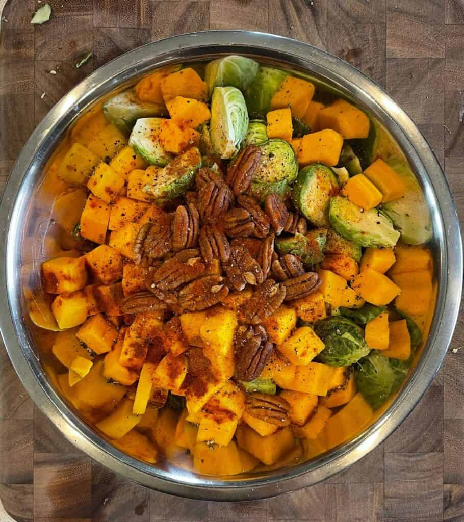 butternut squash, brussels sprouts, pecan halves, olive oil, cinnamon, smoked paprika, and black pepper in a mixing bowl