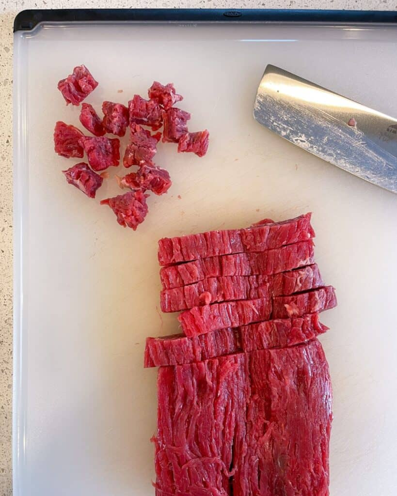 flank steak on a cutting board sliced against the grain and cut into small pieces