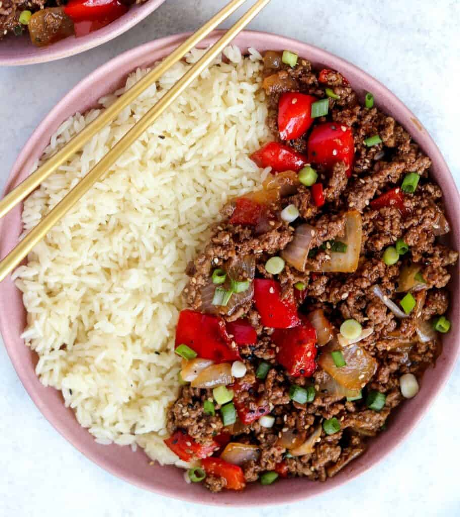 white rice in a pink bowl with the Beijing ground beef topped with scallions and sesame seeds