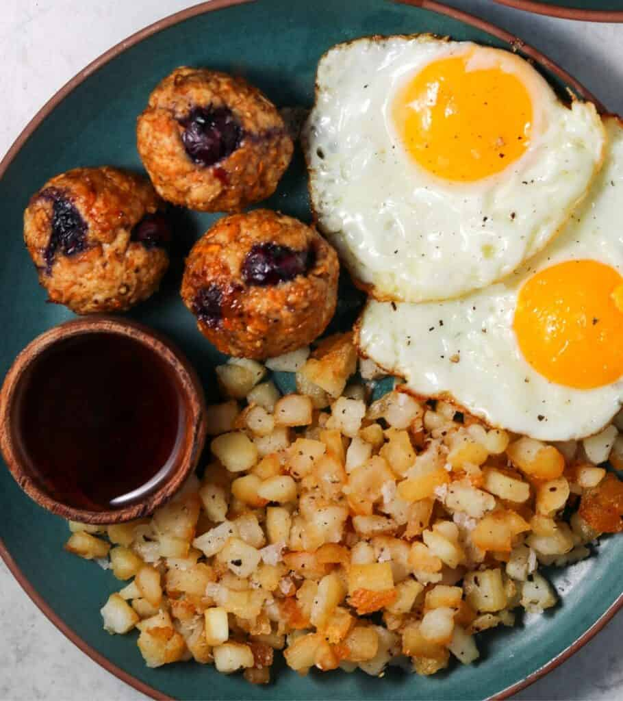 3 breakfast meatballs with fresh blueberries on a green plate with 2 fried eggs, hash browns, and maple syrup