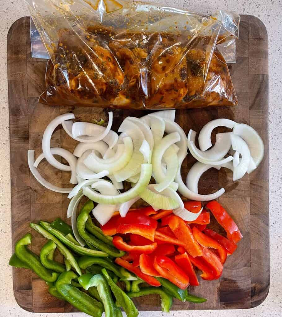sliced bell peppers and onion beside boneless skinless chicken thighs in a marinade