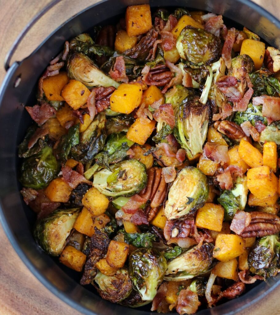 roasted butternut squash, brussels sprouts, pecans, and bacon in an air fryer basket