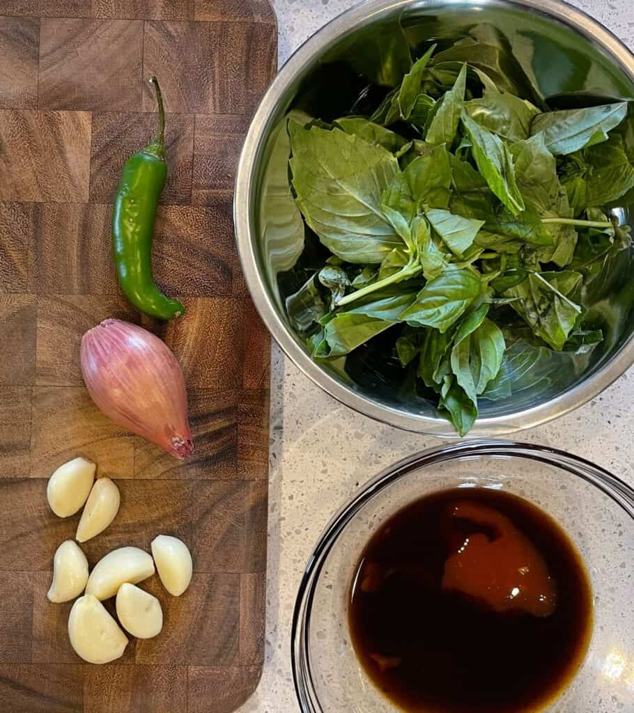 a bowl of basil beside a bowl with the Thai basil chicken sauce and a cutting board with garlic cloves, a shallot, and a serrano pepper