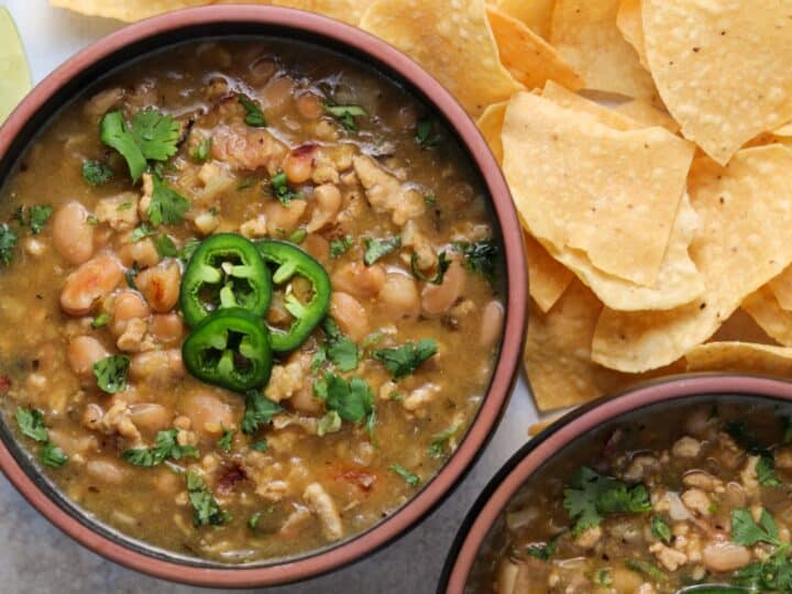 two bowls of white bean ground chicken soup topped with cilantro and slice jalapeño and surrounded by corn tortilla chips