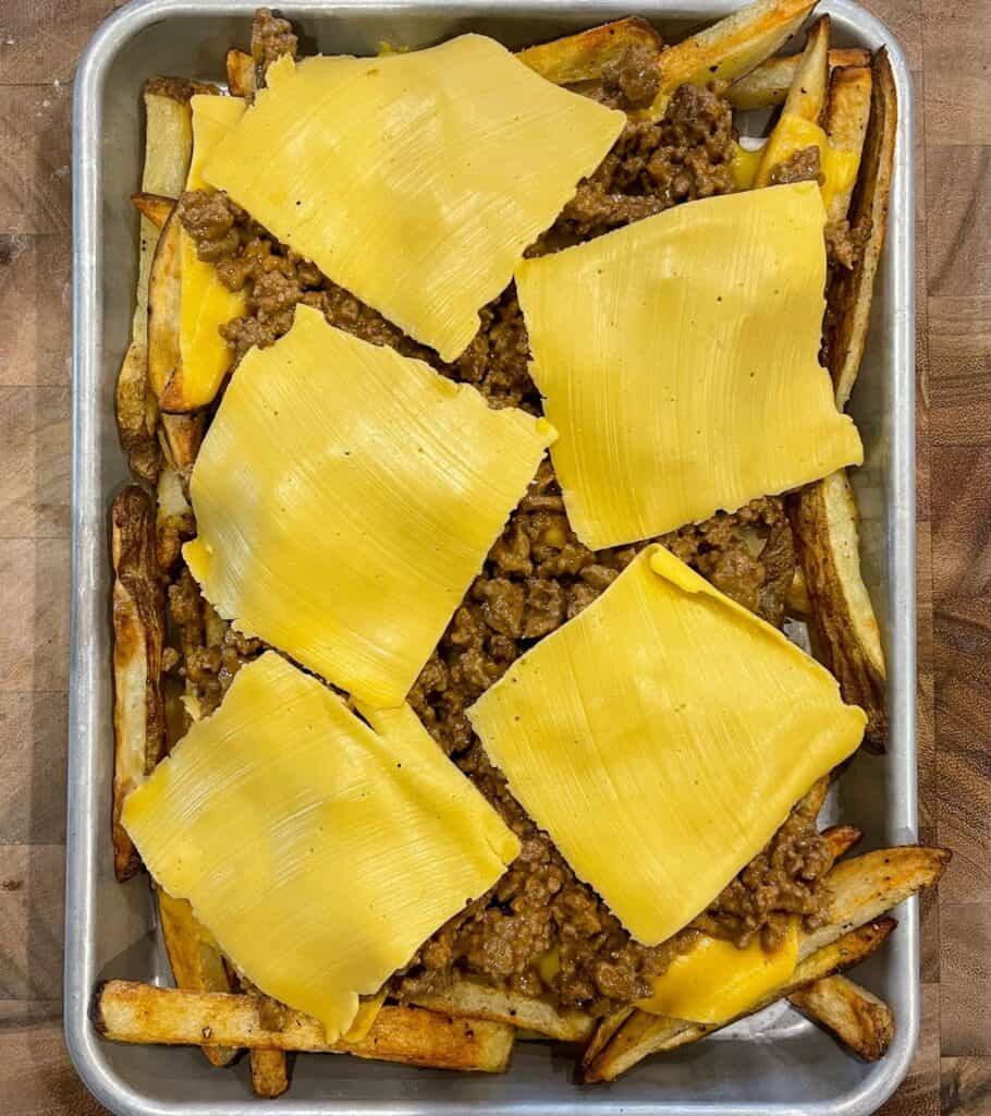 baked fries with cheeseburger toppings before baking