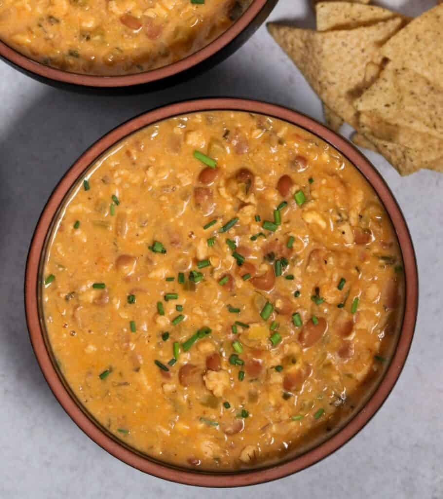 bowl of buffalo ground chicken chili with chives on top and chips on the side