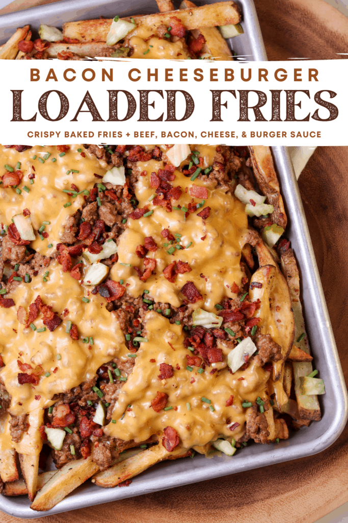 cheeseburger fries on a baking sheet with bacon, chives, and diced pickles